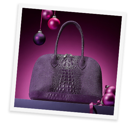 A deep purple crocodile embossed italian suede handbag sits spotlighted atop a dark purple surface against a shaded fuschia backdrop. Three baubles in purple and fuschia hang suspended from the upper left at varying heights on fuschia string and a further two fuschia baubles on ribbon sit next to the handbag
