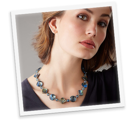 Head shot of a woman in front of a pale grey background shown from the head to shoulders wearing a dark navy blue top and necklace made from blue iridescent paua shell and crystal beads